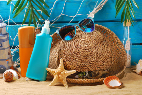 sun protection still life with suntan lotion bottles,straw hat and sunglasses on the beach